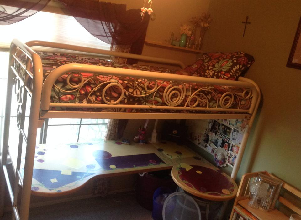 A bunk bed I converted for my daughter years ago. The bottom bunk was removed and made into a desk, I added height to the frame, and added decorative swirls on the sides.