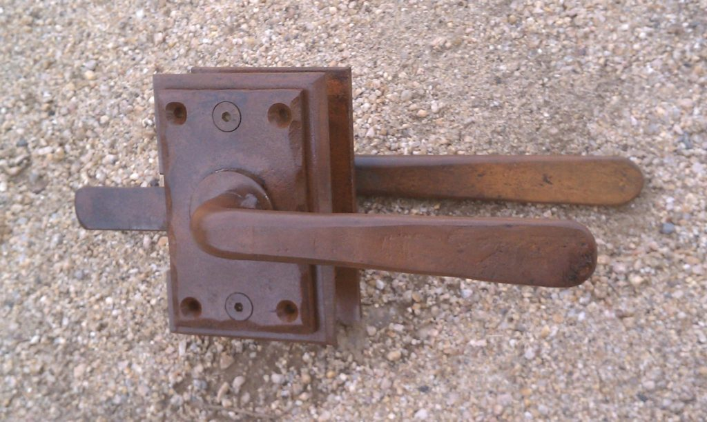 An interesting set of rust finished Colonial style gate latches for a wooden gate downtown in the historic district.