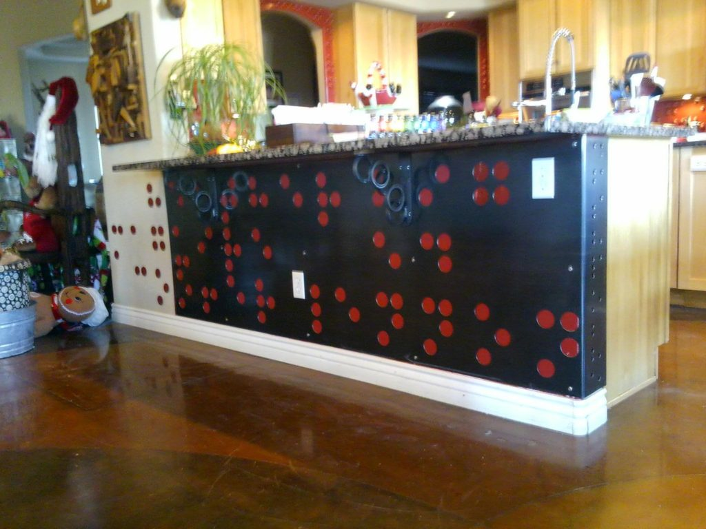 One last installation done before Christmas. This is a piece of hot rolled steel that I machined holes in and faced the pony wall under the granite counter top. The pattern is Braille, and it spells out names. The Braille dots to the left are steel disk that are painted to match the color of the wall behind the steel sheet. Also, on the section that turns the corner there is the Yiddish word for family spelled out in Braille. English Braille though, not Yiddish symbol Braille. The corbel brackets holding up the counter made from circles also have braille on the strip that goes up and down.